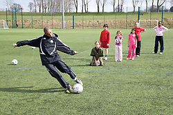 Group of children practicing dribbling a football on a playing field at their local leisure centre,