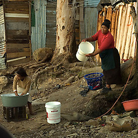 Women wash n Imizamo Yethu shanty town, Hout Bay, Cape Town, South Africa. The work of the CPF and neighbourhood watch have seen the crime rate in Hout Bay drop 63%, but relations between the shanty town of Imizamo Yethu and Hout Bay are tense.  photo  Leonie Marinovich