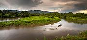 Embera men navigate a log with a piragua down the Rio Sambu in the Darien Province, Panama.