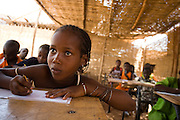 Girl writing in her school book during class at the Tangory Transgambienne 2 primary school in the town of Bignona, Senegal on Wednesday June 13, 2007.
