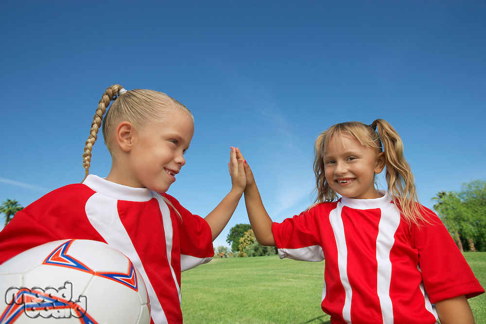 Two girl soccer players (7-9 years) doing 'high five' on soccer field