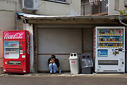 A young Japanese man squats to smoke between vending machines in Machida ward, Tokyo, Japan. Sunday April 26th 2020