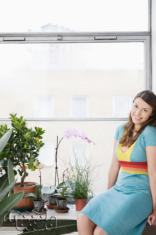 Portrait of young woman sitting on window sill at home