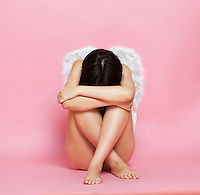 Sad Asian woman with angel wings sitting on floor against pink background