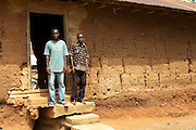 Ben, 25, with his father outside their home in Kromameng, Ghana. Ben doesn't want to take on his fathers cocoa farm and left the community for Accra where he trained to be a hairdresser. He finished his training last year and is now back at home trying to save so that he can return to open up a little barbers shop in the capital.