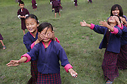 Girl school children play trust games at Wangdue Chhoeling Lower Secondary School, Bumthang, Bhutan..Bhutan the country that prides itself on the development of 'Gross National Happiness' rather than GNP. This attitude pervades education, government, proclamations by royalty and politicians alike, and in the daily life of Bhutanese people. Strong adherence and respect for a royal family and Buddhism, mean the people generally follow what they are told and taught. There are of course contradictions between the modern and tradional world more often seen in urban rather than rural contexts. Phallic images of huge penises adorn the traditional homes, surrounded by animal spirits; Gross National Penis. Slow development, and fending off the modern world, television only introduced ten years ago, the lack of intrusive tourism, as tourists need to pay a daily minimum entry of $250, ecotourism for the rich, leaves a relatively unworldly populace, but with very high literacy, good health service and payments to peasants to not kill wild animals, or misuse forest, enables sustainable development and protects the country's natural heritage. Whilst various hydro-electric schemes, cash crops including apples, pull in import revenue, and Bhutan is helped with aid from the international community. Its population is only a meagre 700,000. Indian and Nepalese workers carry out the menial road and construction work.