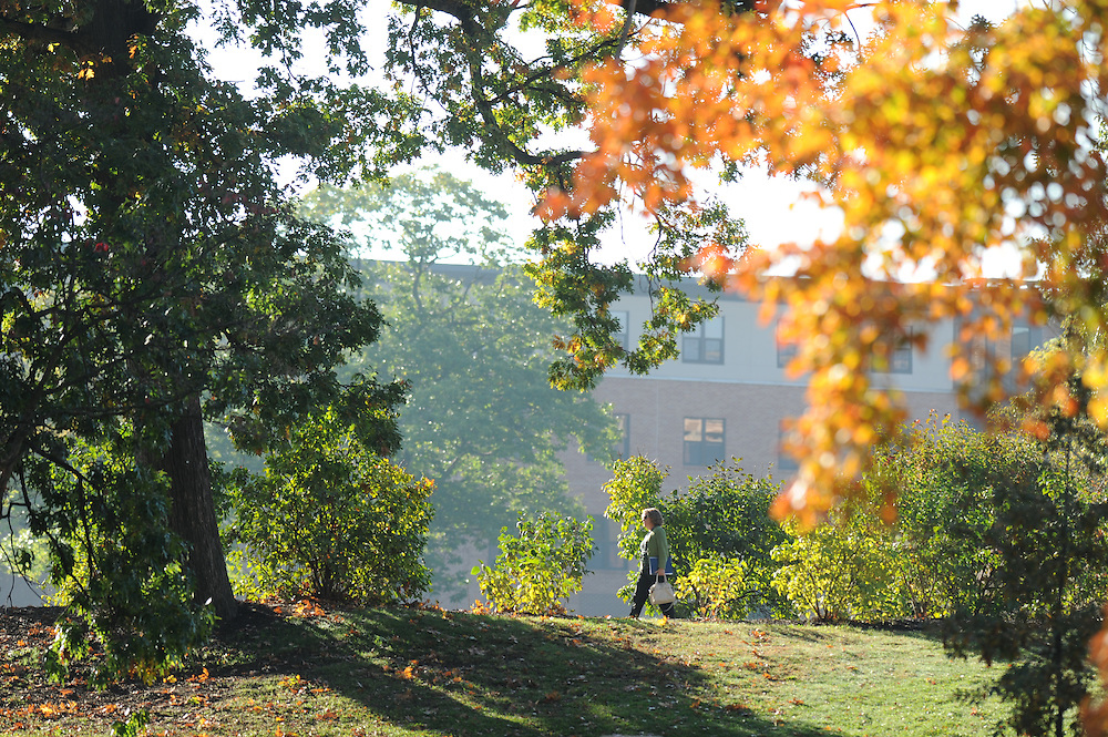 A faculty member walks to class near Oscar Ritchie Hall on a warm fall day.