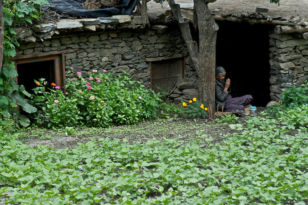 An old woman fixes her hair while sitting in the doorway of her old village home in Nesang Village, Himachal Pradesh, India
