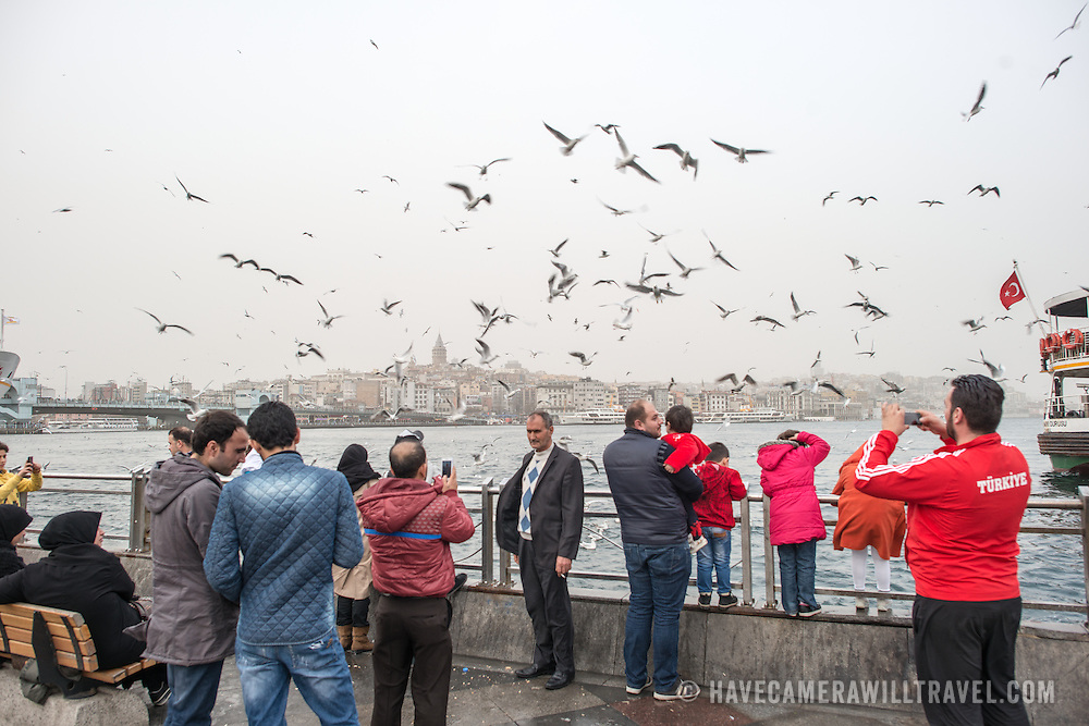 Tourists pose for photos with the seagulls on the waterfront of Eminonu in Istanbul. In the background is the Galata Tower.