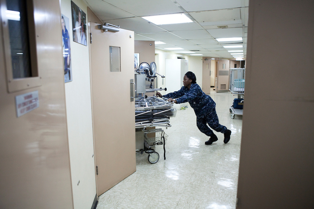 A member of the Navy medical staff moves gurneys on board the USNS Comfort, a naval hospital ship, before its mission to help survivors of the earthquake in Haiti on Monday, January 18, 2010 in the Atlantic Ocean off the coast of the United States.