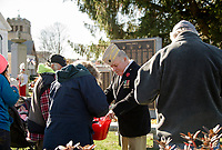"VFW Commander Timm Grant hands out ""Buddy Poppy's"" to folks gathered at Veteran's Square for the Veteran's Day services on Sunday morning.  (Karen Bobotas/for the Laconia Daily Sun)"