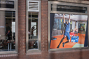 Seen through a window, a lady stretches to echo an image of a man hanging from bars, outside a Fitness First gym, on 1st September 2016, in south London, England UK.