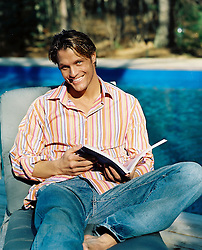 Man smiling sitting on a lounge chair poolside holding a book