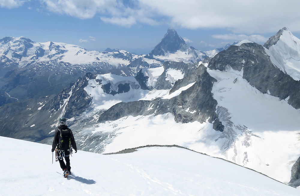 An alpinist descending from Zinal rothorn, 4221m, with Matterhorn in the background.Valais, Switzerland.