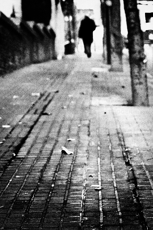 A figure walking into the distance on a pavement