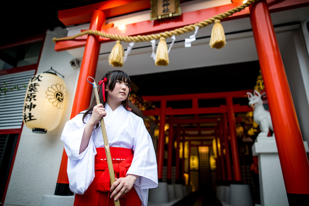 "TOKYO, JAPAN - JUNE 27 : A shrine maiden posed for a portrait in front of the entrance of Akihabara shrine in Akihabara, Tokyo, Japan on June 27, 2016.  A newly opened Akihabara Shrine offers a memorial services for ""deceased"" anime figures. Photo by Richard Atrero de Guzman"