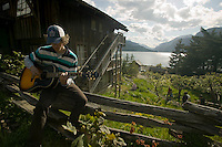 A young man plays his guitar while attending an outdoor course at the well known Strathcona Park Lodge, in Strathcona Park, Central Vancouver Island.  Vancouver Island, British Columbia, Canada.