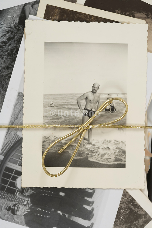 various old family photographs tied together with a golden rope