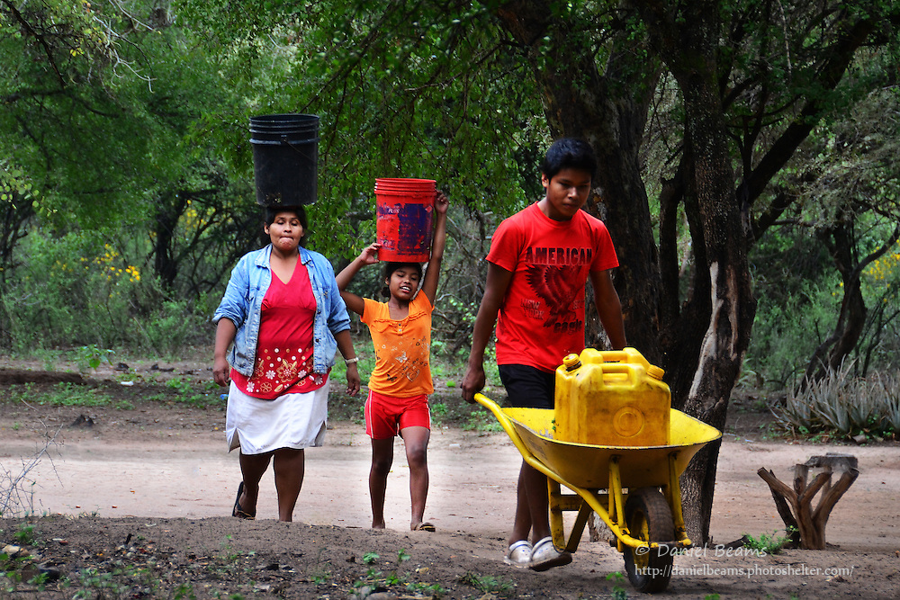 Guarani family carrying water