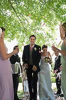 Bride and groom walking on path people throwing flower petals in air