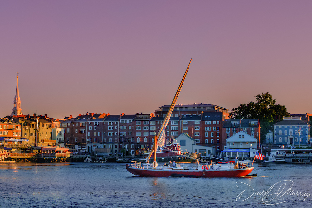 The gundalow Piscataqua sails on the Piscataqua River in front of the downtown Portsmouth area at sunset.