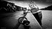 Almost the whole fishing fleet had left the harbour leaving this semi derelict old trawler alone at the bleak quayside in the empty fishing harbour of Newlyn in Penwith, Cornwall