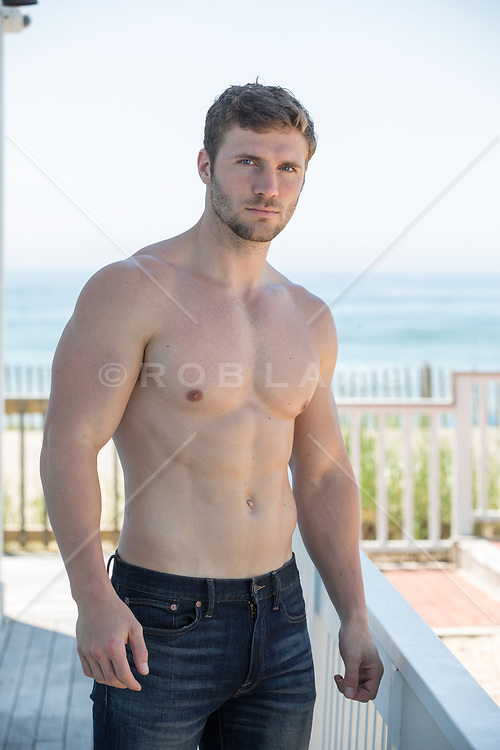 shirtless good looking man in jeans by the ocean