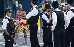 © Licensed to London News Pictures. 28/08/2017. London, UK. A heavy police presence as revellers and carnival goers enjoy the second day of the 2017 Notting Hill carnival. The two day event is the second largest street festival in the world after the Rio Carnival in Brazil, attracting over 1 million people to the streets of West London. Photo credit: Ben Cawthra/LNP