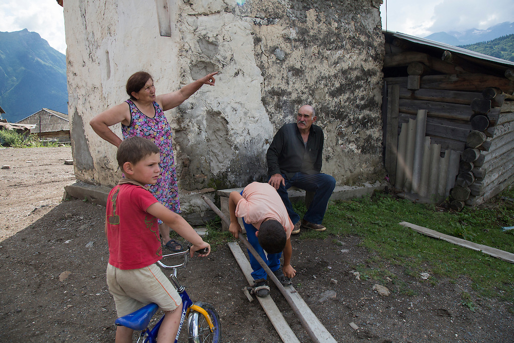 Valery Vipliani and his wife and two of his grandsons in the yard of their house. His wife points out a section of the Transcaucasian Trail that is planned to rise over the house next year. One of his grandsons plays with a pair of homemade wooden skis Valery uses to get around in the winter.