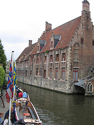 A canal and boats along centuries-old buildings in Bruges, Belguim.