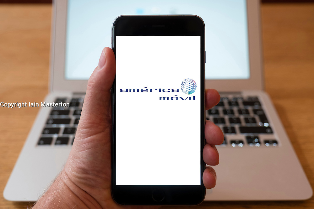 Using iPhone smartphone to display logo of America Movil,  a Mexican telecommunications corporation