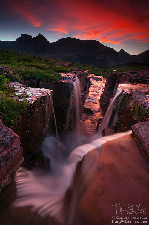 Several small waterfalls combine not far from the Continental Divide near Logan Pass in Glacier National Park, Montana. Several peaks, including Mount Gould and Mount Siyeh, are visible in the background.