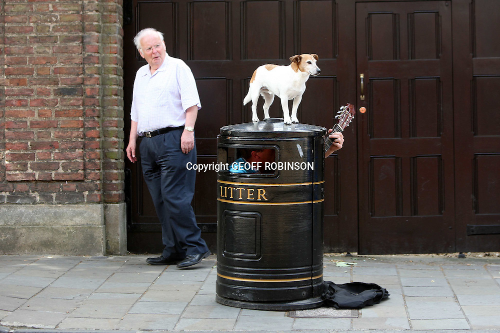 "CHARLIE CAVEY BUSKING IN CAMBRIDGE WITH HIS GUARD DOG OBI..A busker who sings in a BIN has bought a GUARD DOG to protect his takings...Charlie Cavey plays his own form of TRASH metal on his guitar whilst squeezed inside a tiny metal litter bin...At 5ft 9 he finds his job cramped and smelly but his stinky singing style is proving a huge hit with passers-by...The only problem is the 31-year-old can't keep an eye on his money from inside the bin so he has employed Obi the Jack Russell to stand guard...""I have had problems with people taking money as they don't always realise I am in the bin and it looks like free cash,"" he said...""It's quite a struggle to keep getting in and out of the bin so now I bring Obi with me...""He is really good and just stands on top of the bin and watches people going by...""He knows I am inside the bin so he's not worried and he doesn't try to run away.""..Obi is already being likened to Nipper the dog who was painted listening to a wind-up gramophone in the famous picture His Master's Voice - later used by music shop HMV...SEE COPY CATCHLINE Busking bin man's dog"