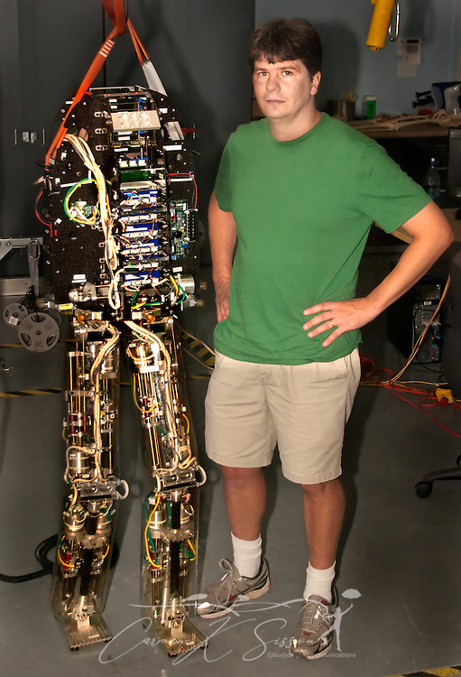Research scientist Jerry Pratt stands beside M2V2, a lifesize bipedal robot, Nov. 13, 2009 at the Institute for Human and Machine Cognition in Pensacola, Fla. M2V2 cost nearly $1 million to build  and is unique because of its ability to mimic human heel-to-toe motion and, when pushed, right itself to prevent a fall. (Photo by Carmen K. Sisson/Cloudybright)