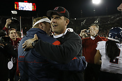 November 6, 2010; Stanford, CA, USA;  Arizona Wildcats head coach Mike Stoops (left) hugs Stanford Cardinal head coach Jim Harbaugh at the end of the game at Stanford Stadium.  Stanford defeated Arizona 42-17.