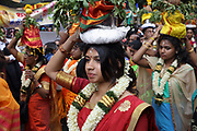 Women carrying coconuts on their heads in the parade celebrating the festival of Ganesh Chaturthi, marking the birth of the Hindu god Ganesha, on the streets of the La Chapelle area of the 18th arrondissement of Paris, France, on Sunday 1st September 2019. Coconuts are broken open to symbolise giving your heart to Ganesha (the shell is the world, the flesh is karma and the water is human ego). The annual religious festivities and parade take place near the Ganesha Temple of Paris, or Sri Manicka Vinayakar Alayam Temple, the largest Hindu temple in France. Ganesha is the elephant-headed Hindu God of Beginnings, son of Shiva and Parvati, who represents love and knowledge. Picture by Manuel Cohen