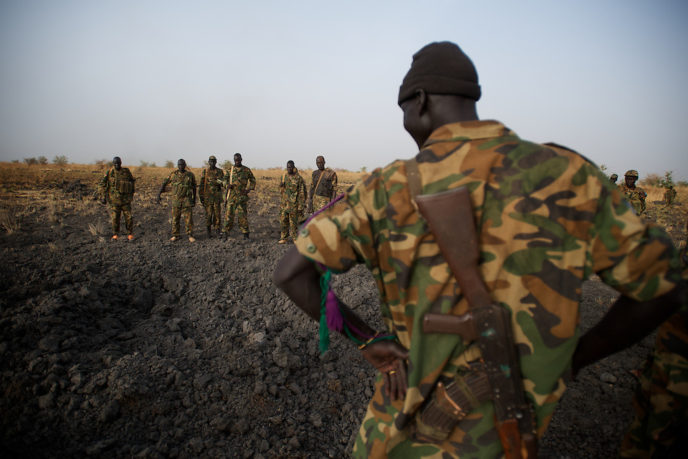 April 24, 2012 - Panakuach, South Sudan: A group of SPLA soldiers stand by the scene where a bomb dropped by the SAF air force landed minutes earlier near the last defensive line outside the village of Panakuach, 70 kilometers north of Bentiu...South Sudan and their northern neighbors, Sudan, have in the past two weeks been involved in heavily clashes over border disputes. Bentiu and neighboring villages have been under constant bombardment by the troops os Karthoum , who established their positions around 10 kilometers into South Sudan's territory. The international community is concerned about the possibility of a full on war between the two countries. (Paulo Nunes dos Santos/Polaris)