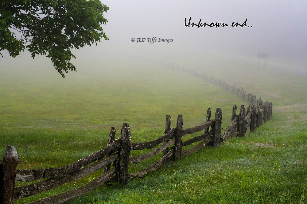 Wood rail fence curving into the distance through a heavy fog