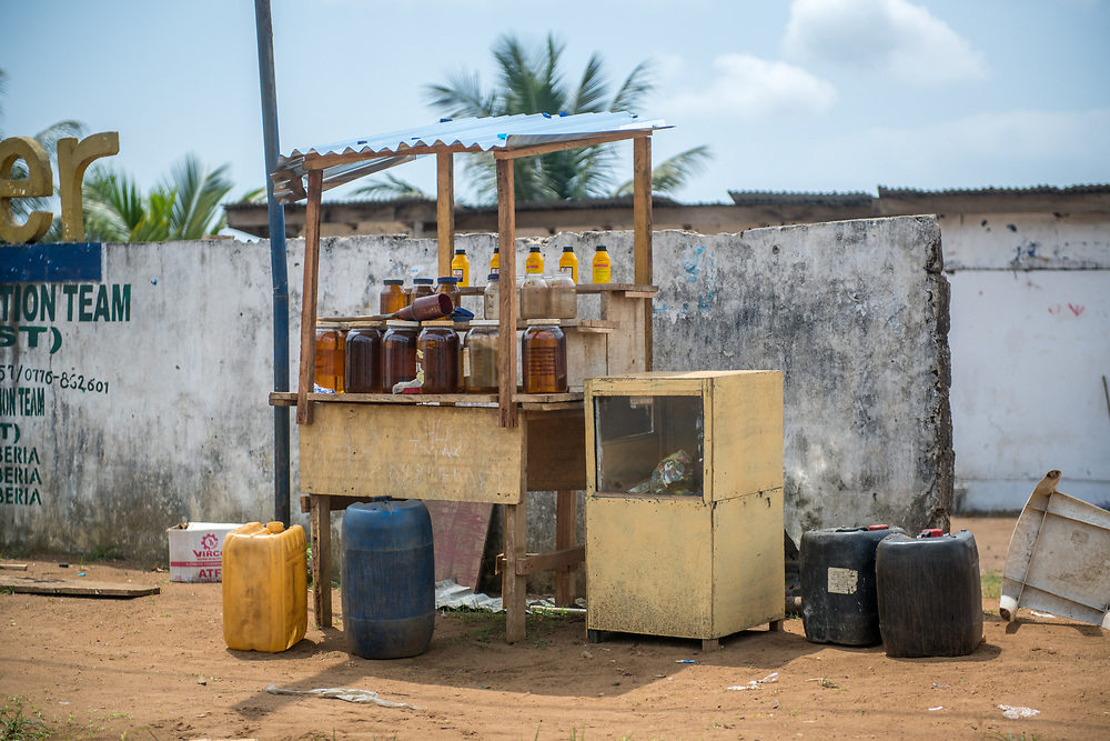 Jars of fuel for sale at a typical Liberian gas station on the side of a road. Monrovia, Liberia