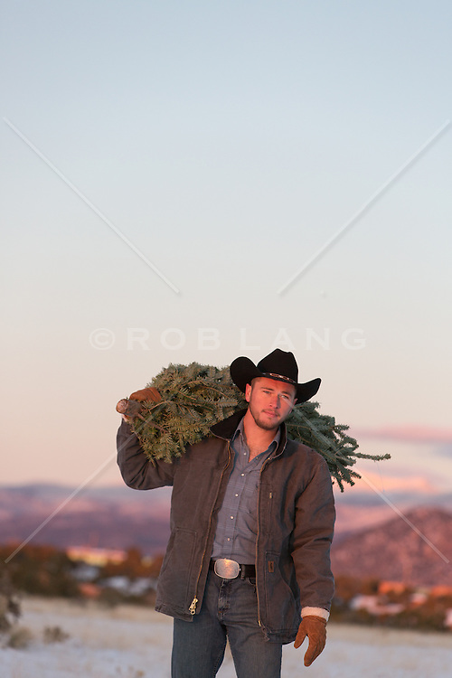 cowboy with a tree over his shoulders in the Winter