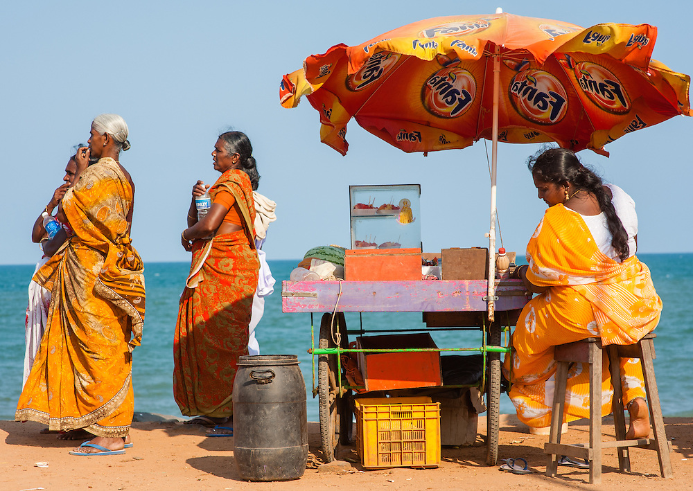 Woman in sari at snack stall with umbrella by the sea in Puducherry (India)