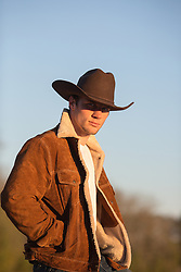 sexy cowboy at sunset in a sheepskin and suede jacket outdoors