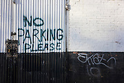 A hand-painted No Parking Please notice on a garage's gates under railway arches in south London.