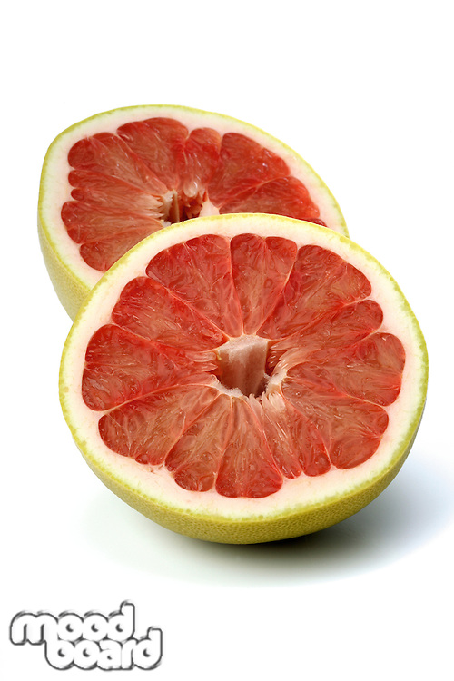 Halved grapefruit on white background