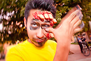 "Oct. 30, 2009 -- PHOENIX, AZ: Zombie MICHAEL GARCIA has a human hand coming out of his head and something stuck in his eye during the Zombie Walk in Phoenix. About 200 people participated in the first ""Zombie Walk"" in Phoenix, AZ, Friday night. The Zombies walked through downtown Phoenix ""attacking"" willing victims and mixing with folks going to the theatre and downtown sports venues.  Photo by Jack Kurtz"