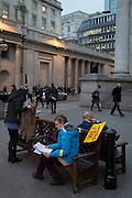 Strangers both using smartphones and ignoring a Wet Paint sign, on 16th February 2017, outside Royal Exchange and the WW1 memorial, in the City of London, England.