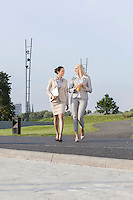 Full length of young businesswomen walking on street