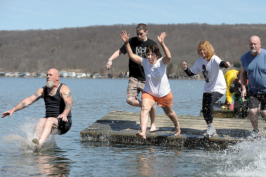 Polar Plungers Mary Helmer (middle), Baily Rose-Gibbs and Charley Sutfin all leap from the Beachcomber docks as Dave Sutfin splashes into the cold waters of Conesus Lake during the 3rd annual Polar Plunge for the Vincent House this past Saturday