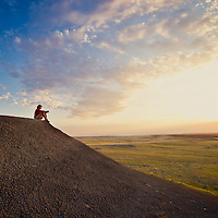 sun setting as woman watches while sitting on a ridge valley county montana