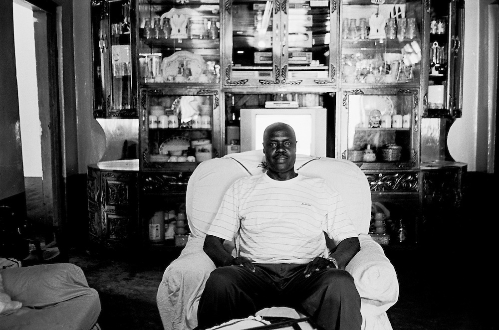 Rulings by the government after Kenya's independence in 1963, changed Kibera's status into an 'unauthorized settlement', rendering the inhabitants of Kibera, including the Nubians, as squatters even though the Nubians were living in Kibera long before anyone else. A Nubian Elder sits in the front room of his family's home in Kibera. His family has lived in Kibera since before WWI.